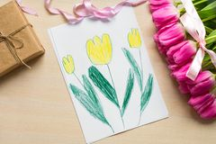 Little boy paints greeting card for Mom on Mother`s Day or 8 March. Top view Royalty Free Stock Photography