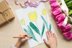 Little boy paints greeting card for Mom on Mother`s Day or 8 March. Top view Stock Photography