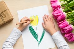 Little boy paints greeting card for Mom on Mother`s Day or 8 March. Top view Royalty Free Stock Image