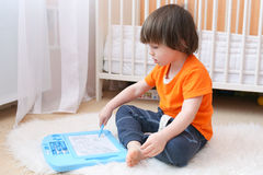 Little boy paints on magnetic tablet Stock Photo