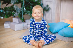 Little boy in pajamas with bears sit on the floor and smile. Hold his legs Royalty Free Stock Photography