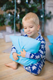 Little boy in pajamas with bears smile, sit and hug blue pillow Stock Photography