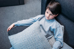 Little boy in pajamas holding pillows while sitting on sofa and looking away. Tired little boy in pajamas holding pillows while sitting on sofa and looking away Royalty Free Stock Photo