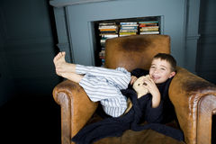 little boy in pajamas lying in chair Stock Image