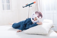 Little boy in pajamas and space helmet lying on pillow Stock Images
