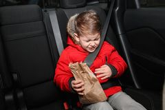 Little boy with paper bag suffering from nausea royalty free stock photos