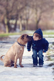 Little boy in the park with his dog friend. Giving him a kiss Royalty Free Stock Photography