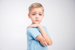 Little boy with patch on elbow. Cute little boywith patch on his elbow sadly looking at camera on white Royalty Free Stock Photos