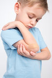 Little boy with patch on elbow. Sad little boy looking at his patched elbow on white Stock Photo