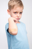 Little boy with patch on elbow. Sad little boy showing patch on elbow and looking at camera on white Royalty Free Stock Image