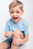 Little boy with patch on knee Stock Images