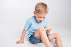 Little boy with patch on knee Royalty Free Stock Photo
