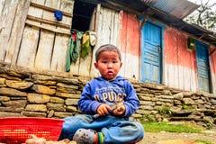 Little boy pealing potatoes in Nepal Stock Photos