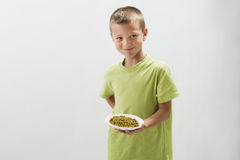 Little boy with peas. Making negative facial expression Royalty Free Stock Photography
