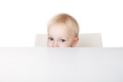 Little boy peeking behind a table Stock Image