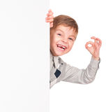 Little boy peeking from blank board Royalty Free Stock Photos