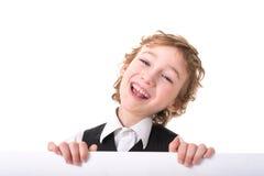Little boy is peeking from blank sign. Portrait of a gay boy six years in the studio Stock Photos