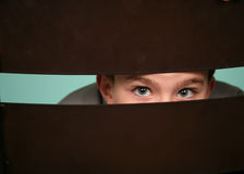 Little boy peeking out. With only eyes visible royalty free stock photo