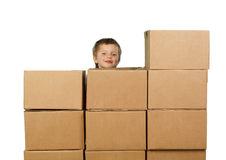 Little boy peeking out from behind boxes Royalty Free Stock Photo