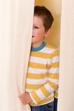 Little boy peeking out from behind the curtains. Royalty Free Stock Photos