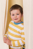 Little boy peeking out from behind the curtains. The boy with the white-and-yellow striped shirt peeking from behind the curtains royalty free stock photography