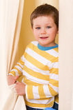 Little boy peeking out from behind the curtains. The boy with the white-and-yellow striped shirt peeking from behind the curtains royalty free stock image