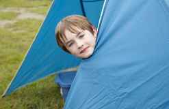 Little boy peeking out from tent Royalty Free Stock Photography