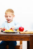 Little boy peeling apple cooking at home. Royalty Free Stock Photography