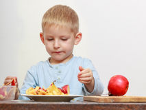 Little boy peeling apples with knife and eating Stock Photos