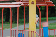 Little boy peeping on the children`s playground.  stock photos