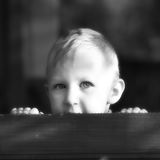 Little boy peeping 3. Cute little boy peeping in the garden. Black and white photo stock photography