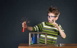 Little boy performing experiments. Crazy scientist.