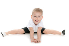 Little boy performs gymnastic exercises Stock Images