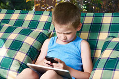 Little boy with phone and tablet pc Stock Images