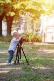 Little boy photographing on the camera on tripod in the park. Two years old boy is photographer. Little boy photographing on the camera on tripod in the park royalty free stock image