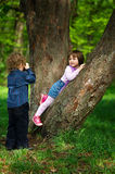 Little boy photographing girl in the park on tree Stock Photos