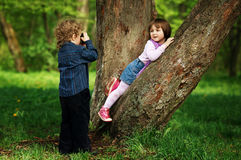 Little boy photographing girl in the park on tree Stock Photography