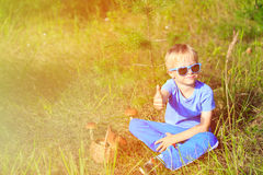 Little boy picking mushrooms in green forest Royalty Free Stock Image