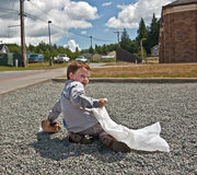 Little Boy Picking up Garbage. This 4 year old Caucasian boy is picking up garbage outside, a crumpled paper bag litter into a white trash bag. He's helping the stock photography