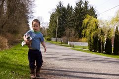 Little Boy Picking Up Litter on Roadside. This photo captures a cute little boy picking up litter on the side of a road.  He's wearing his cowboy boots as he's Stock Photography