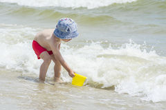 Little boy picking up sea water into a bucket for the game against the backdrop of the waves, Stock Photo
