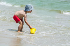 Little boy picking up sea water into a yellow bucket for the game against the backdrop of the waves. Royalty Free Stock Photo