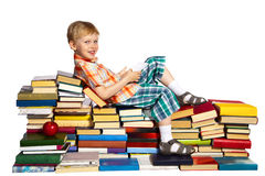 Little boy on a pile of books Stock Images