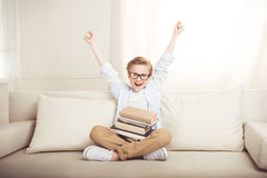 Little boy with pile of books sitting on sofa with raised hands Royalty Free Stock Photography