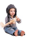 Little boy with pilot hat playing toy plane Stock Images