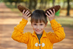 Little boy with pinecones in park Royalty Free Stock Photos