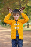 Little boy with pinecones in park Stock Images