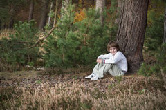 Little boy in a pinewood forest sitting among pine cones. On autumn day Royalty Free Stock Image