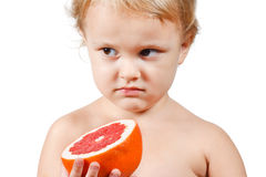 Little boy with a pink grapefruit Stock Photo