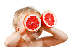 Little boy with a pink grapefruit Royalty Free Stock Photos